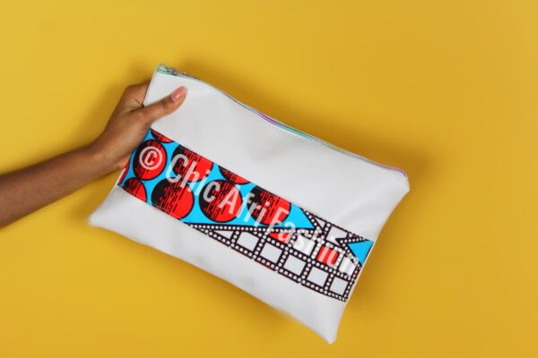 Hand Holding A cream color Clutch Bag with hints of African Prints fabric