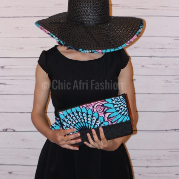Woman Wearing a floppy had and holding a denim clutch with a hint of African prints