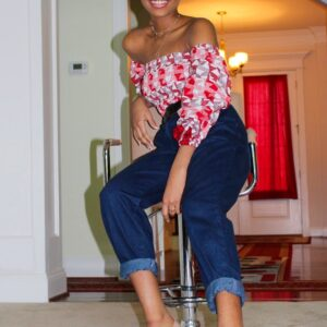 Woman Smiling and sitting on a stool wearing a red off-shoulder African prints Top