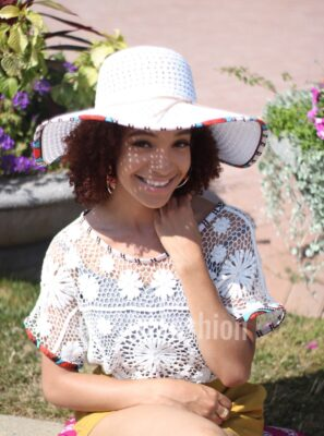 Woman Smiling Wearing a lace crochet top and a straw hat made with a hint of African Prints Fabric