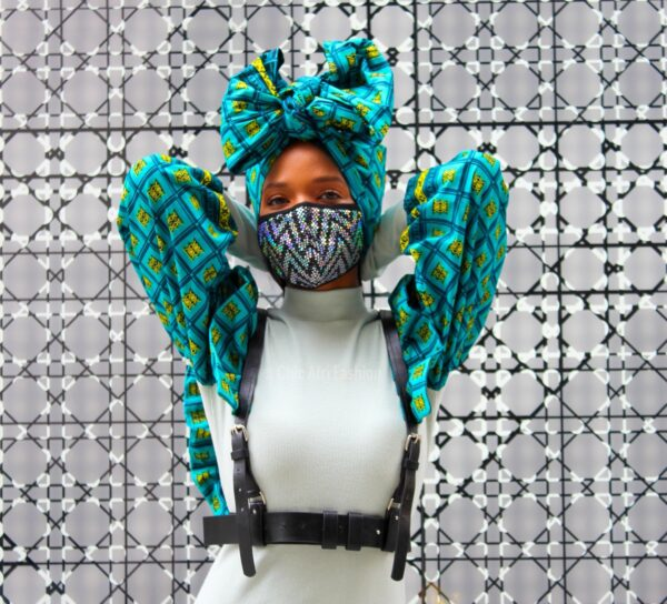 Black woman wearing a mask and African print headwrap