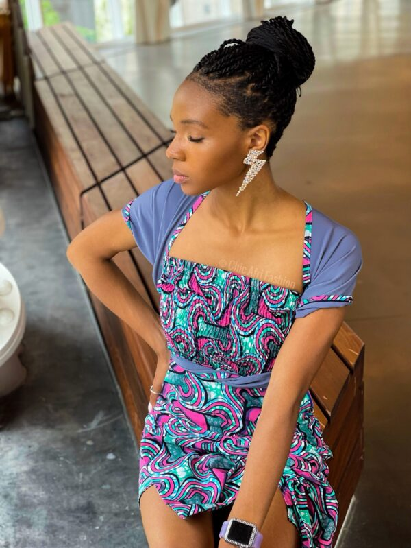Black Woman Sitting and wearing Blue and Pink African print top and skirt